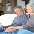 Senior couple surfing on internet at home — Stock Photo