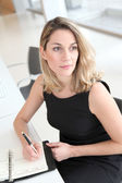 Businesswoman writing appointment on agenda — Stock Photo