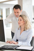 Office workers in front of desktop computer — Stock Photo