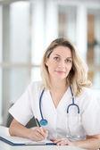 Hermosa enfermera en hospital escribiendo en bloc de notas — Foto de Stock