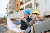 Architect and engineer looking at plan on construction site — Stock Photo