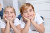 Blond children laying in sofa with hands on chin — Stock Photo