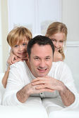 Portrait of father with children up on his back — Stock Photo