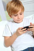 Portrait of little blond kid playing video game — Stock Photo
