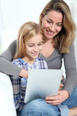 Mother and daughter using electronic tab — Stock Photo