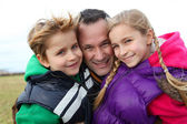 Portrait of man with 2 children out in the countryside — Stock Photo