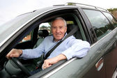 Elderly man driving a car — Stock Photo