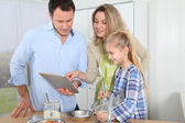 Parents and daughter preparing meal in home kitchen — Stock Photo