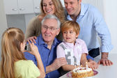 Little girl taking picture of family on birthday celebration — Stock Photo