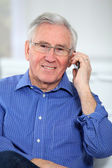 Elderly man talking on mobile phone — Stock Photo
