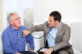 Doctor examining elderly man's health — Stockfoto