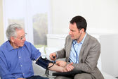 Doctor taking old man's blood pressure — Stock Photo