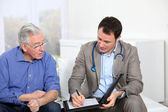 Doctor writing medical prescription to elderly man — Stock Photo