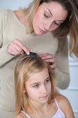 Mother treating daughter's hair against lice — Stock Photo
