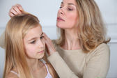 Mother treating daughter's hair against lice — Fotografia Stock