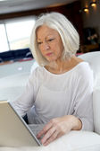 Senior woman surfing on internet at home — Stock Photo