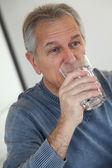 Senior man drinking glass of water — Stock Photo
