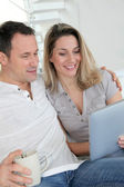 Couple at home using electronic tablet — Stock Photo