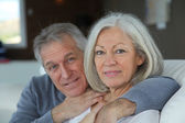 Senior couple sitting in sofa at home — Stock Photo
