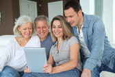 Portrait of happy family sitting in sofa with electronic tablet — Stock fotografie