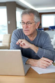 Senior man at home in front of laptop computer — Stock Photo