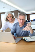 Senior couple making secured payment on internet — Stock Photo