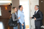 Real estate agent showing modern house to couple — Photo