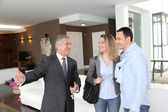 Real estate agent showing modern house to couple — Stock Photo