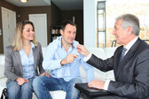Real-estate agent giving house keys to young owners — Stock Photo