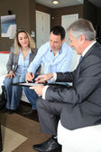 Couple with real-estate agent signing home investment contract — Stock Photo