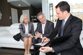 Senior couple signing financial contract for property purchase — ストック写真