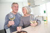 Senior couple drinking wine in home kitchen — Stock Photo