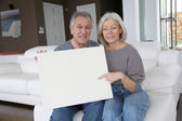 Senior couple holding message board — Stock Photo