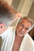 Senior man looking at hair in mirror — Stock Photo