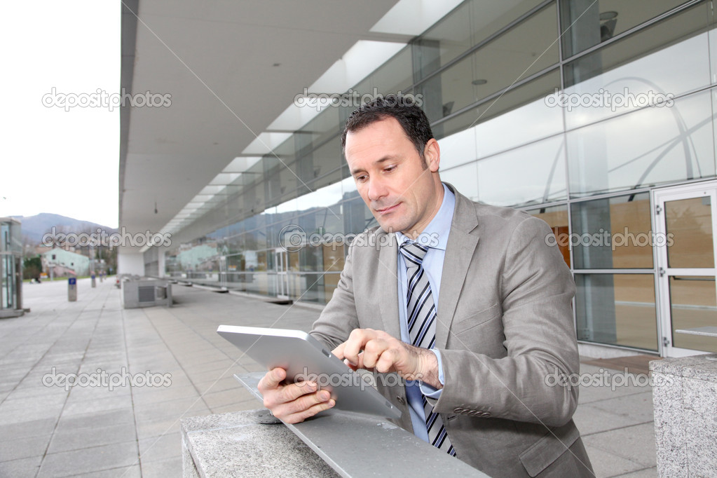 Businessman using electronic tab outside congress center  Stock Photo #6697766