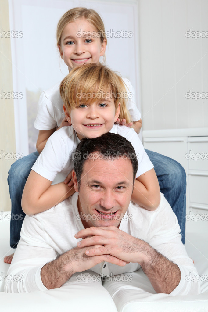 Portrait of father and children laying in sofa  Stock Photo #6698191