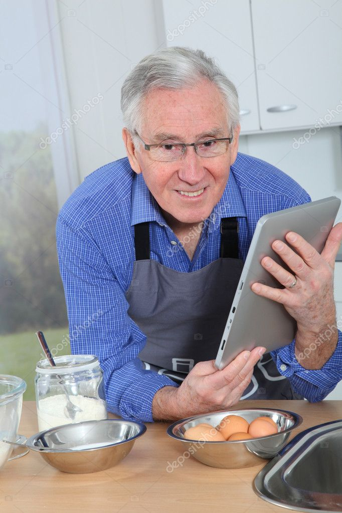Elderly man looking at recipe on electronic tab — Stock Photo #6698499