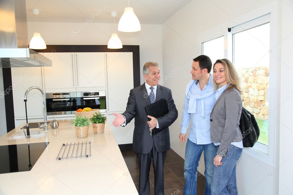 Real estate agent showing modern house to couple stock for Modern house estate agents