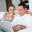 Couple relaxing in sofa with laptop computer — Stock Photo #6700033