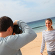 Man taking picture of girlfriend at the beach — Stock Photo