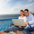Happy couple using electronic tablet by swimming-pool — Stock Photo #6700521