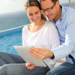 Happy couple using electronic tablet by swimming-pool - Stock Photo