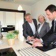 Real-estate agent showing interior of house to senior couple — Stock Photo