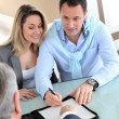 Happy couple signing purchase contract — Stock Photo
