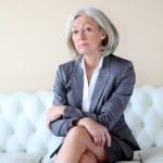 Senior woman sitting in white sofa — Stock Photo