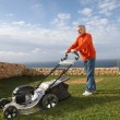 Senior man mowing the lawn — 图库照片