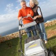 Stock Photo: Senior couple mowing lawn
