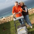 Stock Photo: Senior couple mowing the lawn