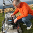 Foto Stock: Senior man mowing the lawn
