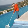 Senior couple cleaning swimming pool — Stock Photo #6700648
